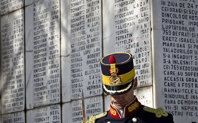 An honor guard soldier stands during a ceremony at a Jewish cemetery in Bucharest, Romania in February 2012, next to a monument bearing the names of Romanian Jewish refugees killed in 1942 aboard the SS Struma. Around 792 people drowned after the ship was struck by a Soviet torpedo (AP Photo/Vadim Ghirda)