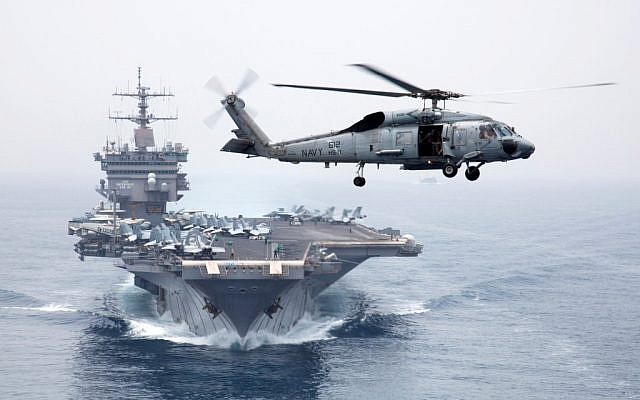 A Sea Hawk helicopter flies in front of the 5th Fleet's USS Enterprise. (photo credit: CC BY Official U.S. Navy Imagery, Flickr)