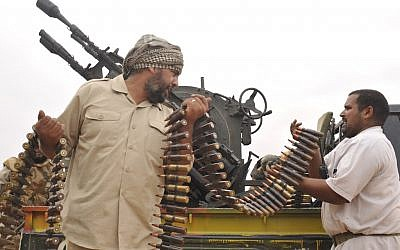 Libyan revolutionary fighters load their machine gun during an attack against pro-Gadhafi forces in 2011. (photo credit: AP/Bela Szandelszky)