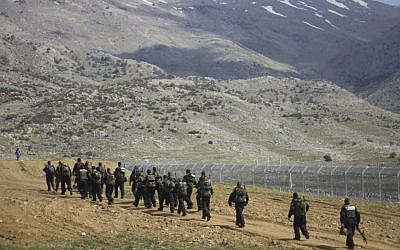 Israeli riot police men march along the border between Majdal Shams in the Golan Heights, and Syria in March. (AP Photo/Ariel Schalit)