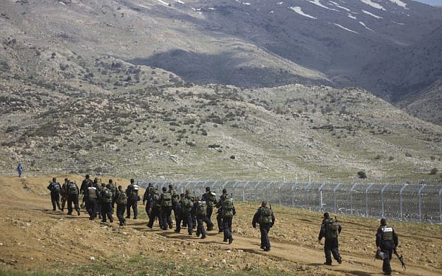 Israeli riot police men march along the border between Majdal Shams in the Golan Heights, and Syria, as security is tightened ahead of Land Day on Friday. (AP Photo/Ariel Schalit)