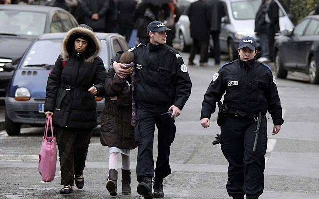 A student (second from left) is flanked by an unidentified woman and police officers as they leave the scene of the Toulouse shooting on Monday (photo credit: AP/Manu Blondeau)