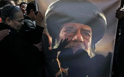 Coptic mourners kiss a picture of the late Pope Shenouda III (photo credit: AP/Nasser Nasser)