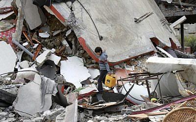 A Palestinian boy walks through the rubble of a destroyed building following an Israeli air strike in Jabaliya, on Monday (photo credit: AP Photo/Adel Hana)