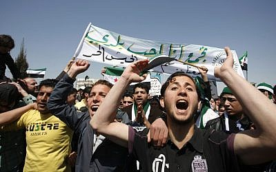"Syrians chant anti-Assad slogans in front of the Syrian embassy during a protest in Amman, Jordan, on Friday. The Arabic banner reads, ""I love my country and the Free Syrian Army."" (photo credit: AP Photo/Mohammad Hannon)"