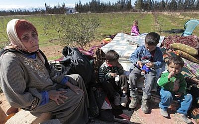 A Syrian woman who fled from the Syrian town of Qusair, near Homs, is seen with her family at the Lebanese-Syrian border village of Qaa, Monday, March 5, 2012. (photo credit: AP Photo/Hussein Malla)