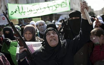 A woman holds a machine gun during an anti-government rally in a town in northern Syria, Friday, March 2, 2012. (photo credit: AP Photo/Rodrigo Abd)