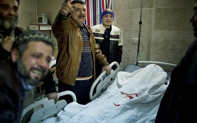 Relatives mourn the death of a victim of a Syrian Army sniper on Wednesday (photo credit: AP/Rodrigo Abd)