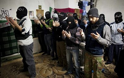 Free Syrian Army fighters pray in Idlib, north Syria, on Thursday (photo credit: AP Photo/Rodrigo Abd)
