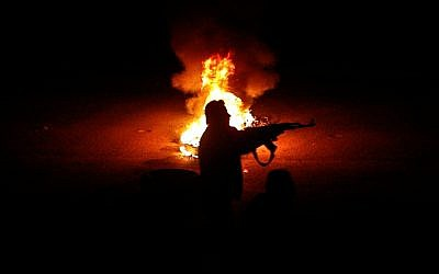 A Syrian rebel fires at a Syrian army checkpoint in a suburb of Damascus (photo credit: AP)