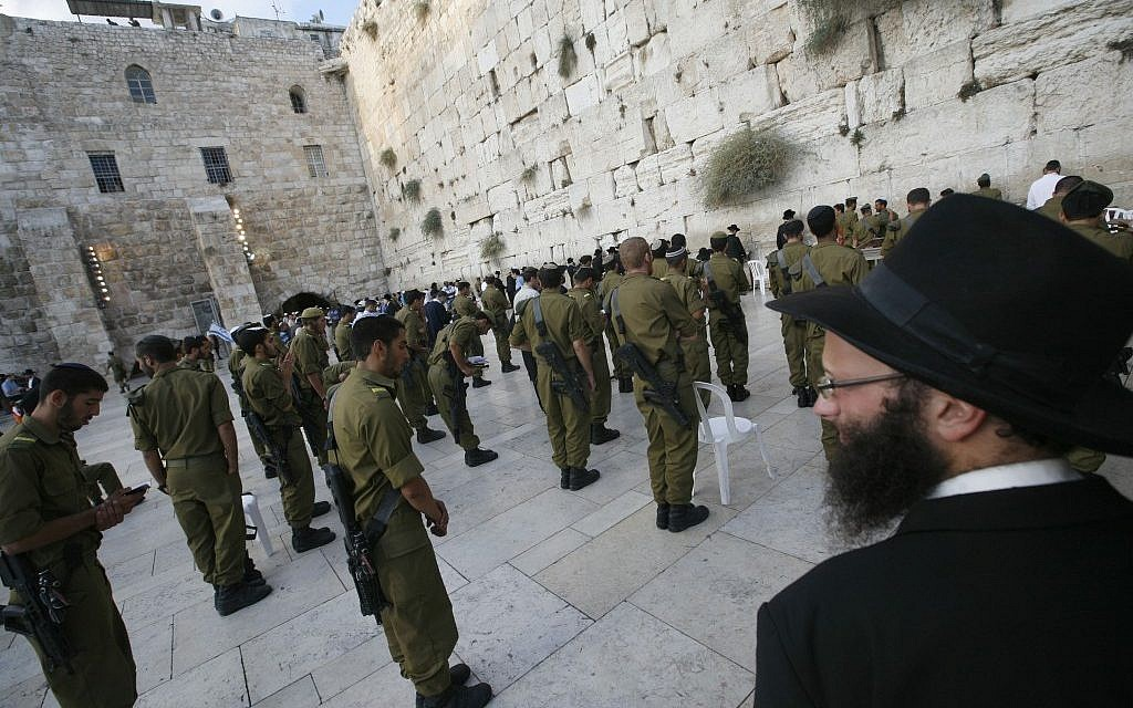An ultra-Orthodox man looks at Golani soldiers praying at the Western Wall (photo credit: Miriam Alster/Flash90)