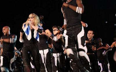 Madonna, wrapped in an Israeli flag, performing at Ramat Gan stadium during her Sticky and Sweet Tour in 2009. (photo credit: Nir Hindi/Flash90)