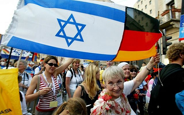 A German Christian raises an Israeli-German flag in the air during the Feast of the Tabernacles in Jerusalem (photo credit: Olivier Fitoussi/Flash90)