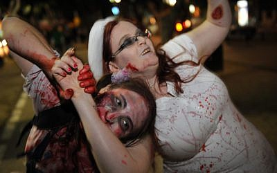 A young woman sinks her teeth into celebrating Purim (photo credit: Gili Yaari/Flash 90)