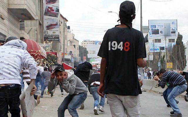 Stone-hurling Palestinians clash with Israeli troops near the Qalandiya checkpoint on 'Nakba Day' last May. (photo credit: Nati Shohat/Flash90)