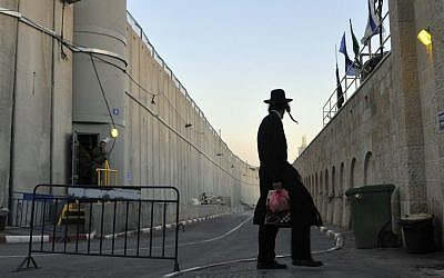 A man walks past the security barrier near Rachel's Tomb, on the outskirts of Bethlehem  (photo credit: Serge Attal/Flash90/File)