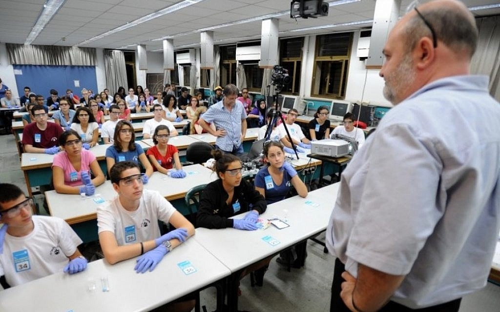 "Students participate a mass chemistry experiment in Tel Aviv University last September, a re-enactment of an experiment performed in the space shuttle Columbia in 2003 by the first Israeli astronaut in space – the late Colonel Ilan Ramon. The re-enactment, one of 13 conducted at Israeli institutions, was part of an attempt to break the Guinness World Record for ""largest chemistry lesson at multiple venues."" Guinness presented the award to the participating institutions last November (photo credit: Gili Yaari/Flash90)"