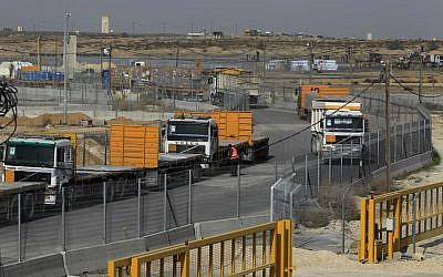 Empty trucks from Gaza wait to be loaded with goods (left) as full trucks drive toward Gaza in the background at the Kerem Shalom crossing between Israel and Gaza last year (Tsafrir Abayov/Flash90)
