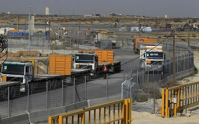 Empty trucks from Gaza wait to be loaded with goods (left) as full trucks drive toward Gaza in the background at the Kerem Shalom crossing between Israel and Gaza last year (photo credit: Tsafrir Abayov/Flash90)