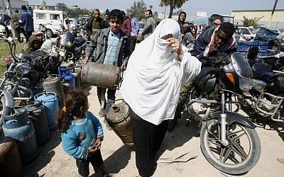 A Palestinian woman carries a gas canister in Khan Younis, Gaza Strip (photo credit: Abed Rahim Khatib/Flash90)