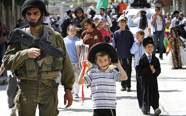 Soldiers guard Purim celebrants in the West Bank city of Hebron on Thursday. (photo credit: Miriam Alster/Flash90)