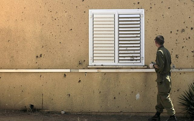 An Israeli soldier examines a house hit by a mortar shell in March (photo credit: Tsafrir Abayov/Flash90)