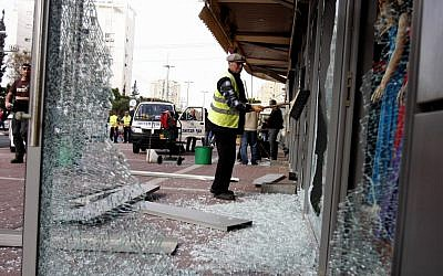 Cleaning up after a Grad rocket fired from Gaza hits the center of Ashdod last Monday. (photo credit: Flash90)*