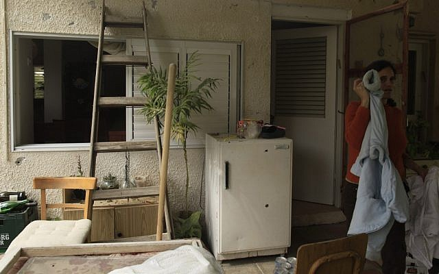 An Israeli woman stand near the entrance to her house in a Gaza border kibbutz, hit by a Kassam rocket earlier this week. (photo credit: Tsafrir Abayov/Flash90)