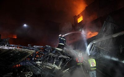Palestinian fire fighters try to extinguish a blaze at a burning factory after an Israeli missile strike in the east of the Gaza Strip early on Wednesday. (photo credit: Wissam Nassar/Flash90
