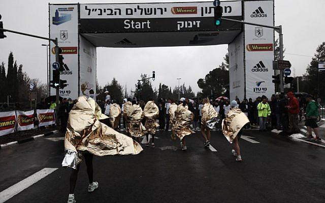 Runners in ponchos at the start of the Jerusalem Marathon (photo credit: Kobi Gideon/Flash90)