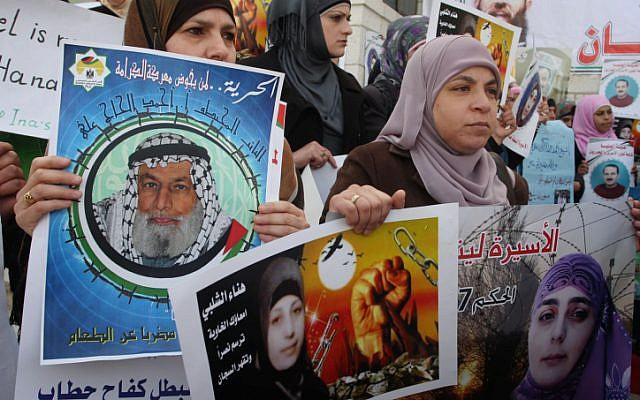 Palestinian women hold posters of Hana Shalabi (photo credit: Issam Rimawi/Flash90)