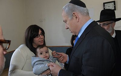 Prime Minister Benjamin Netanyahu visits Eva Sandler, wife of Rabbi Jonathan Sandler and mother of Arieh and Gabriel, the victims of Monday's shooting in Toulouse. March 22, 2012. (photo credit: Amos Ben Gershom/GPO/FLASH90)