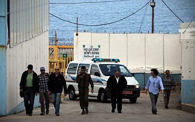 Ahmed Jamal Daif (2nd L), escorted by Israeli officers, arrives at the border crossing between Israel and Lebanon, in March 2012 (photo credit: Avishag Shaar Yashuv/Flash90)