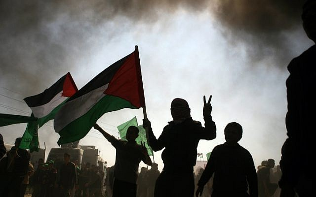 Palestinian protesters waving Palestinian flags during a rally marking Land Day in the northern Gaza strip, near the Erez crossing between Gaza and Israel, Friday (photo credit: Mustafa Mohamad/Flash90)