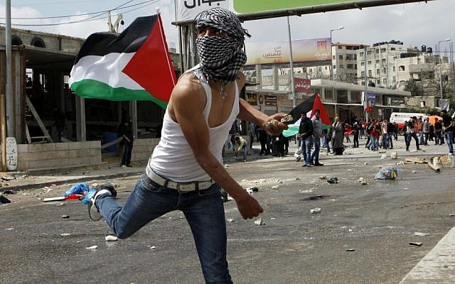 Palestinian youths hurl stones at Israeli troops at the Qalandiya checkpoint. (photo credit: Uri Lenz/Flash90)