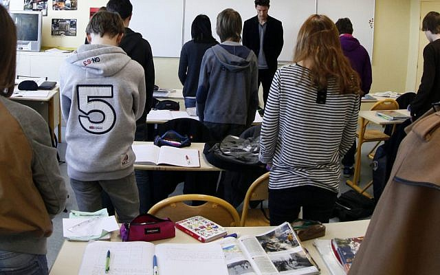 French students in a moment of silence the day after gunman Mohamed Merah murdered three children and a teacher at the Ozar Hatorah school in Toulouse, March 2012 (photo credit: Michel Spingler/AP)