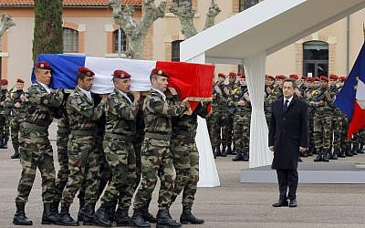 French President Nicolas Sarkozy stands by soldiers carrying a coffin during a ceremony to pay homage to the three soldiers believed killed by Mohamed Merah (photo credit: AP/Jacques Brinon)
