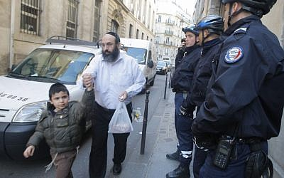 Illustrative photo: A schoolchild and his father leave a Jewish school in Paris, watched by police officers, March, 2012. (photo credit: Jacques Brinon/AP)