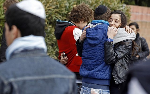 Students comfort each other at the Ozar Hatorah Jewish school where a gunman opened fire killing four people in Toulouse, on March 19, 2012. (AP/Remy de la Mauviniere)