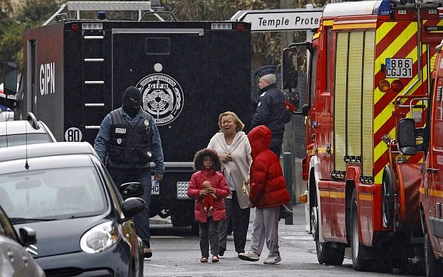A woman and children are escorted by a police officer near a building where Mohammed Merah was holed up Thursday. (photo credit: AP/Remy de la Mauviniere)