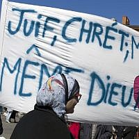 "Illustrative: Following a lethal shooting last year at a Jewish school in Toulouse, French mourners carry a banner that reads, ""Jews, Christians, Muslims: Same God, Love."" (Thibault Camus/AP)"