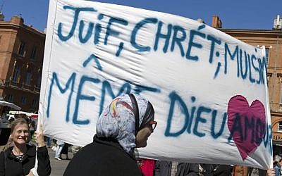 "Following a lethal shooting last year at a Jewish school in Toulouse, French mourners carry a banner that reads, ""Jews, Christians, Muslims: Same God, Love."" (Thibault Camus/AP)"