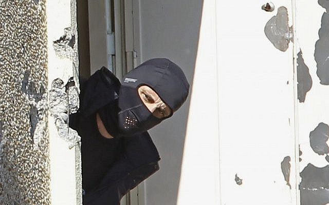 A masked police officer searches for clues at Mohamed Merah's apartment building in Toulouse in March. (Remy de la Mauviniere/AP)
