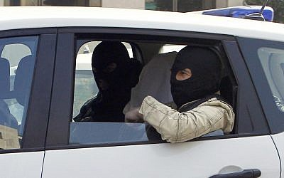 An unidentified man with his head covered, believed to be Abdelkader Merah or his companion, sits between masked police officers as they head to the French police's anti-terrorist headquarters in Levallois-Perret, outside Paris, Saturday, March 24. (photo credit: AP/Christophe Ena)