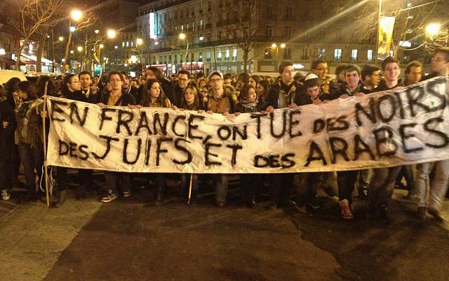 """Protesters raising a banner reading """"in France, we kill Blacks, Jews, and Arabs"""" during a silent demonstration in Paris in March. (Photo credit: Daniel Hoffman)"""