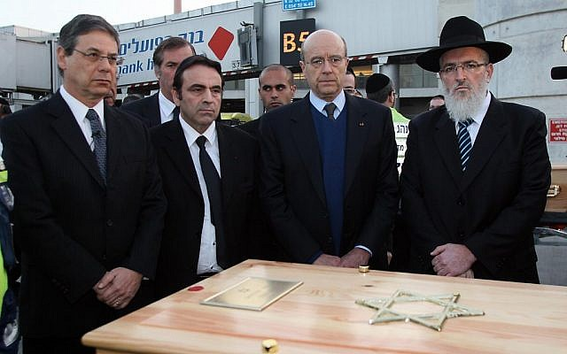 Deputy FM Danny Ayalon and French FM Alain Juppe stand behind one of the coffins at Ben-Gurion Airport (photo credit: Gideon Marcovitch/Foreign Ministry)