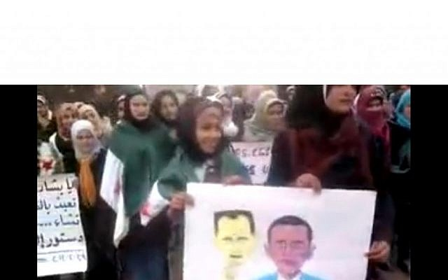 Female student protesters hold a poster of Obama with an Assad mask in Idlib, Syria (photo credit: Shaam News)