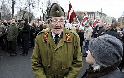 An elderly Latvian takes part in a ceremony to honor soldiers who fought in a Waffen SS unit during World War II, in Riga, Latvia, on Friday. (photo credit: AP/Roman Koksarov)