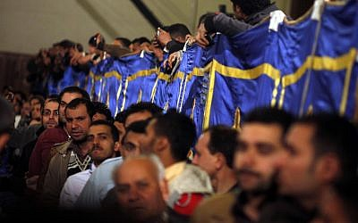 Coptic Christians wait in line to pay respects to the body of Pope Shenouda III Sunday (photo credit: Khalil Hamra/AP)