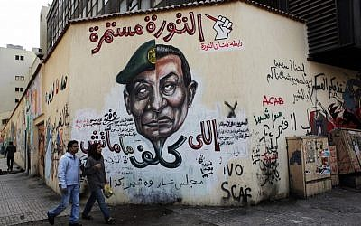 An Egyptian couple walks past a mural depicting military ruler Field Marshal Hussein Tantawi on the left side of the face and ousted president Hosni Mubarak on the right side, with Arabic that reads, 'Who assigned you did not die, No for gas export to Israel, the revolution continues,' at Tahrir Square in Cairo. (photo credit: AP/Nasser Nasser)